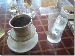 Le café coule lentement dans la tasse, le verre avec glacon attend sagement à coté